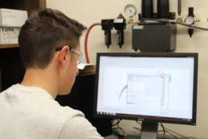 student with lab glasses looking at data on a computer