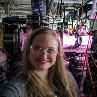 Vanessa Orr in front of a purple plasma discharge in the Woods Lab